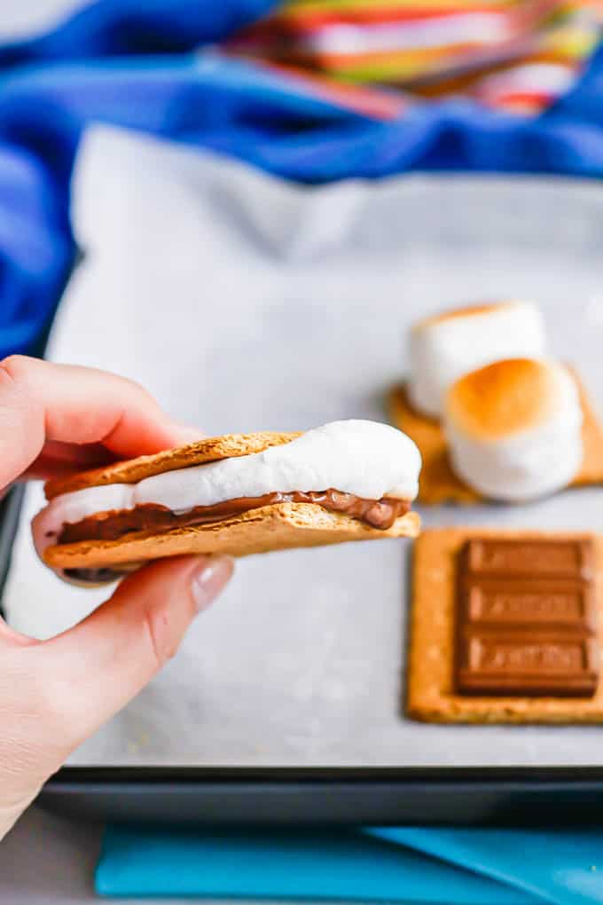A hand picking up a s'mores sandwich from a parchment paper lined baking sheet