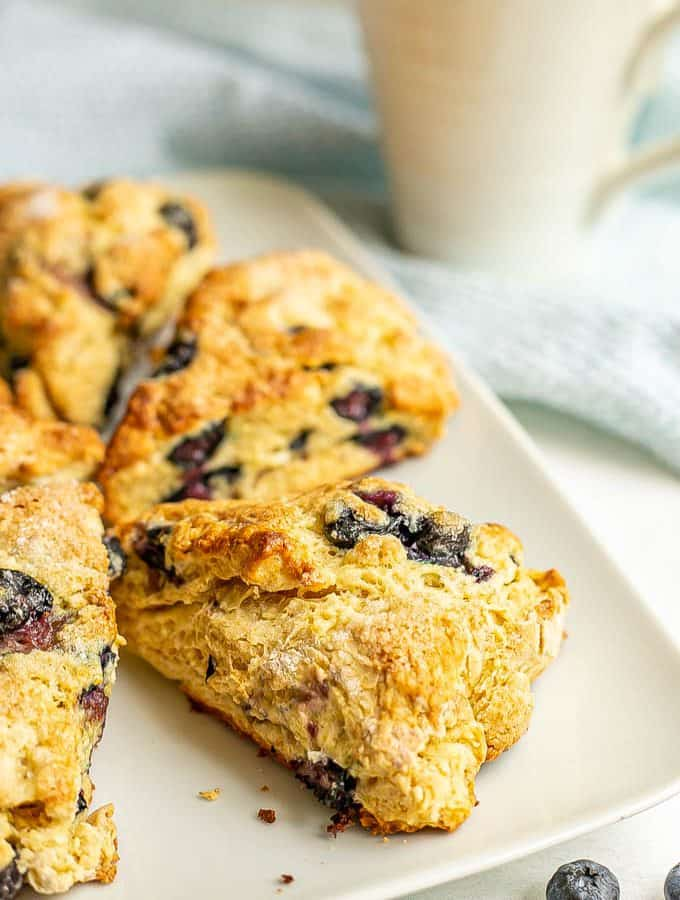 A white serving plate with triangular blueberry scones with a coffee mug in the background