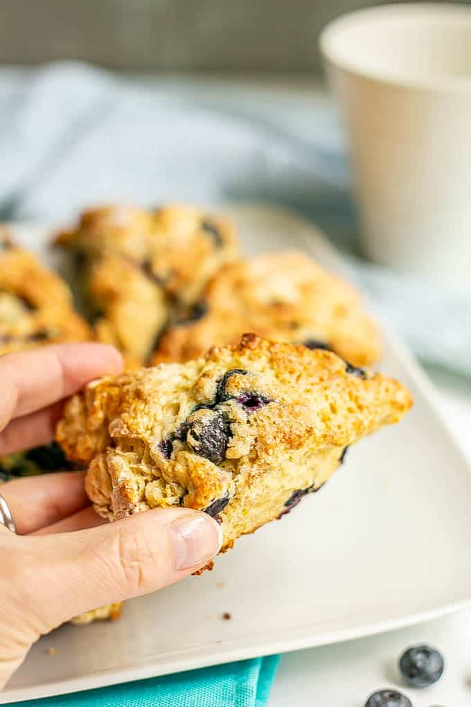 A hand picking up a golden brown blueberry scone from a plate