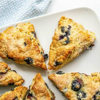 Overhead shot of a plate full of blueberry scones with fresh blueberries scattered nearby