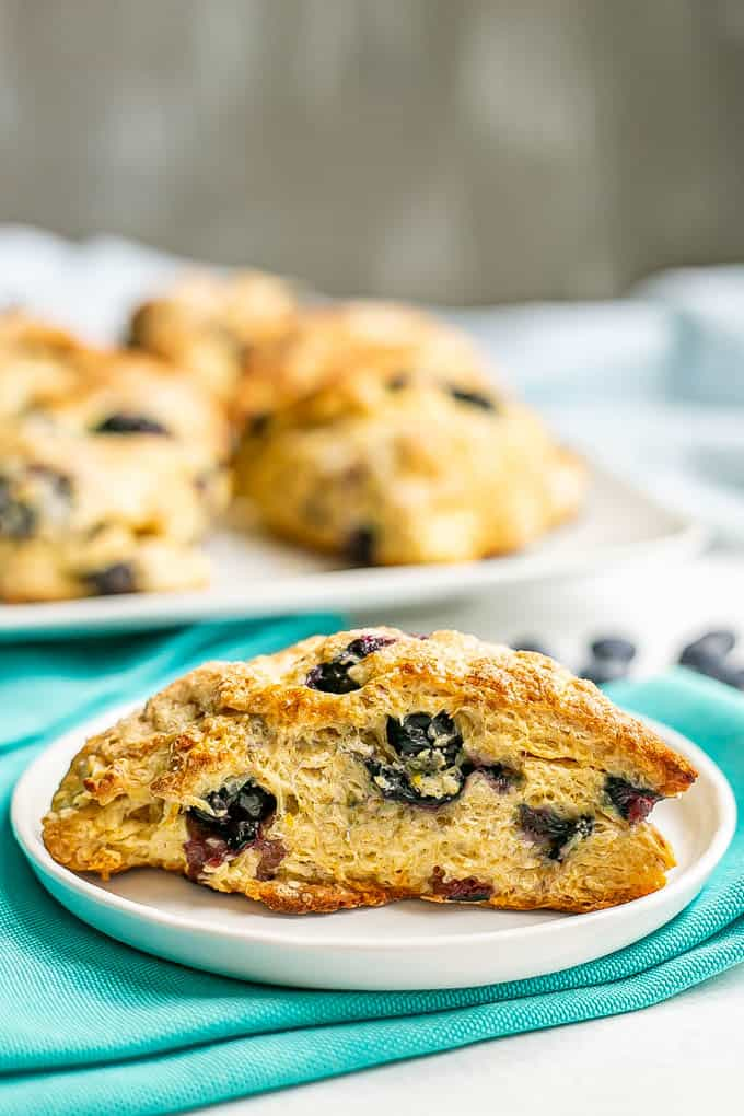 A side angle close up of a baked blueberry scone full of fresh blueberries set on a white plate with turquoise napkins