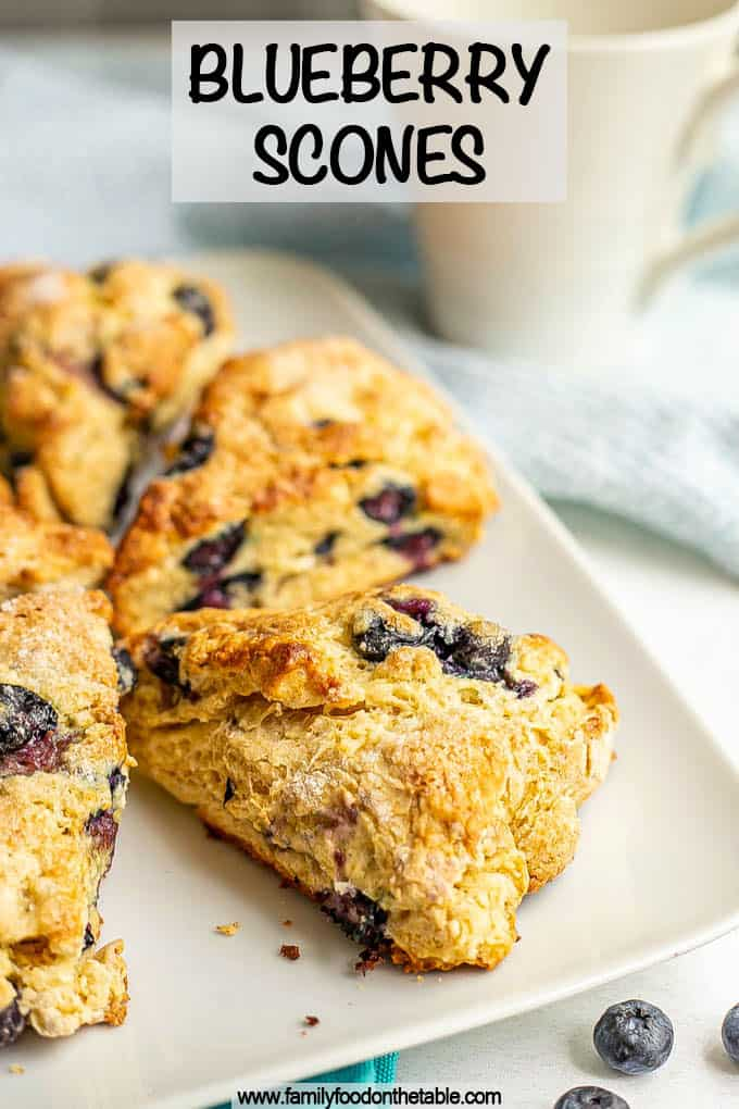 A white serving plate with triangular blueberry scones with a coffee mug in the background and a text overlay on the photo