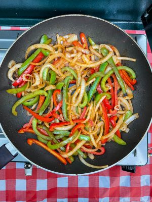 Mixed onions and peppers in a skillet on a camp stove for a chicken fajita camping dinner