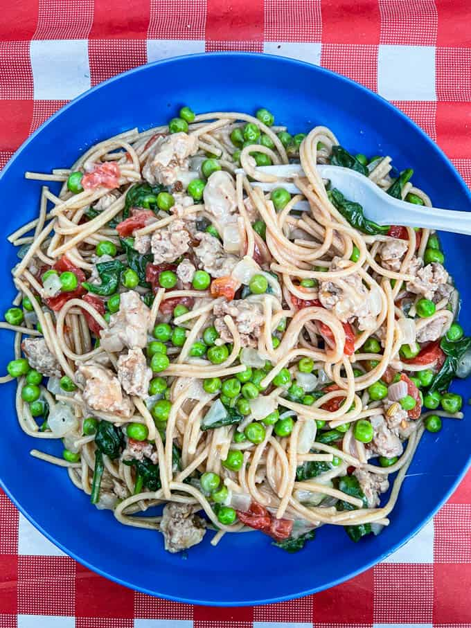 A blue plate with a mix of pasta, turkey sausage, spinach, peas and tomatoes for a camping dinner