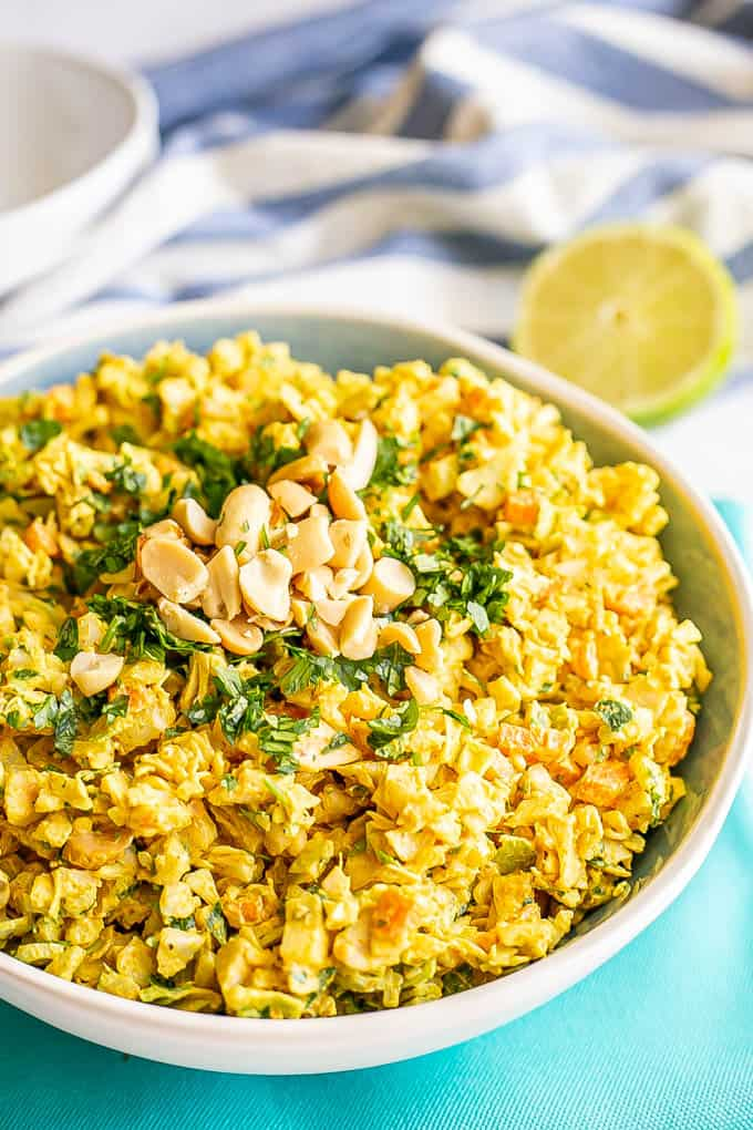 Golden curried coleslaw in a blue and white serving bowl with peanuts and cilantro on top and a halved lime in the background