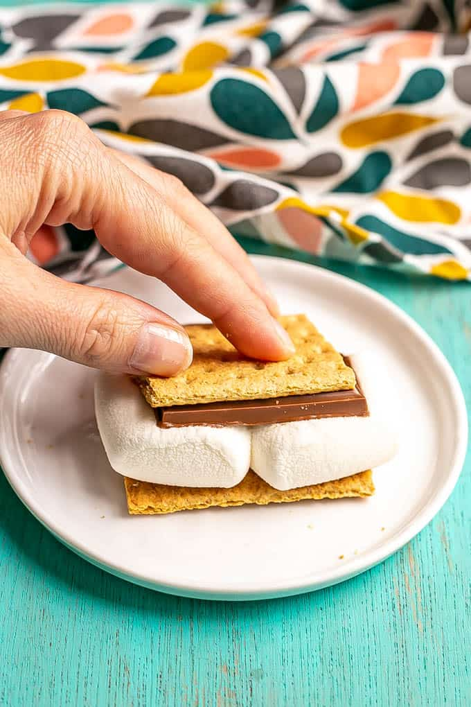 A hand pressing down on an assembled s'mores sandwich after it's been softened in the microwave
