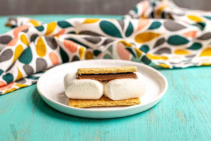 A single s'mores on a small white plate with a colorful napkin in the background