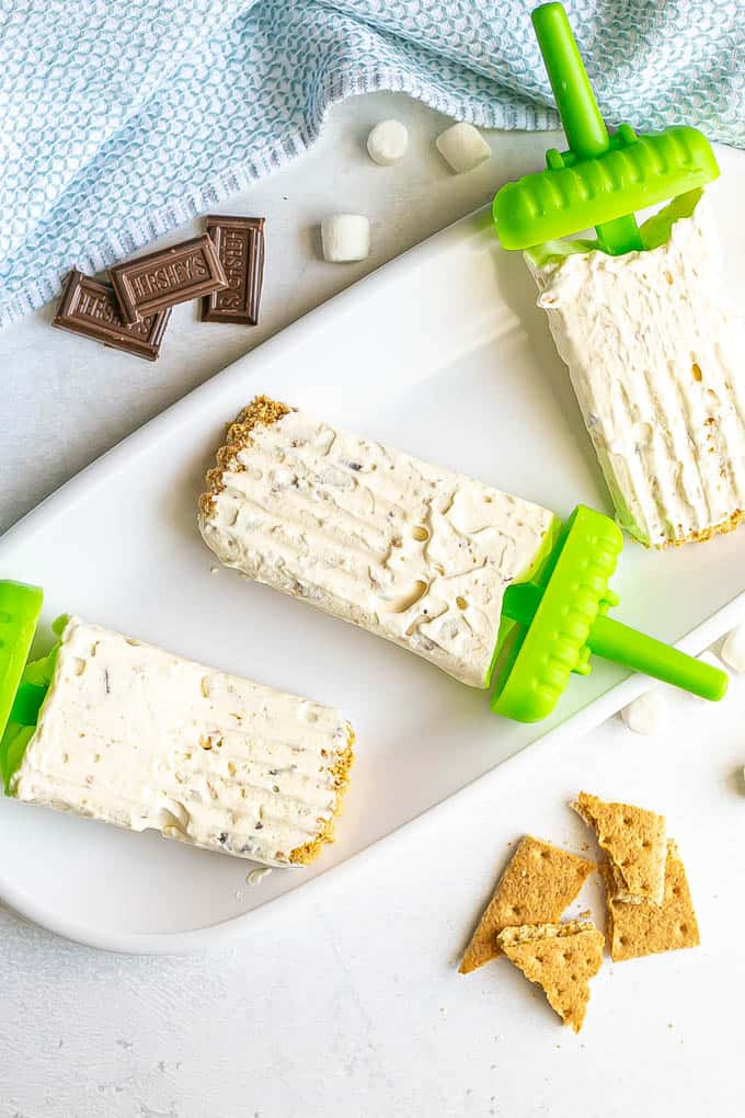 Three s'mores popsicles laid out on a white platter with graham crackers, mini marshmallows and chocolate pieces nearby