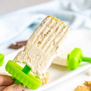 A hand holding a homemade s'mores popsicle with a green stick base and graham cracker crumbs on the top