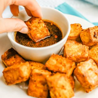 A hand dipping a crispy tofu piece into a soy sauce dipping sauce