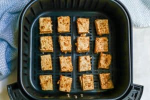 Tofu cubes lined up in an Air Fryer before being cooked