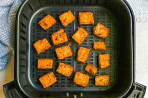 Cubes of tofu in an Air Fryer tray after being cooked