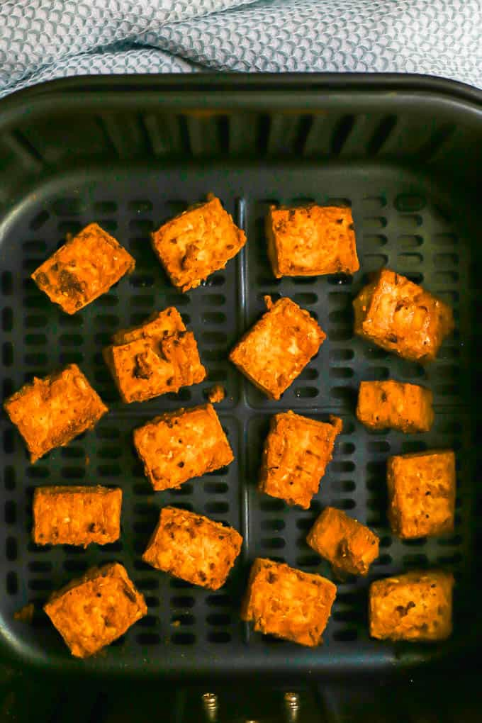 Crispy tofu pieces in an Air Fryer tray after cooking