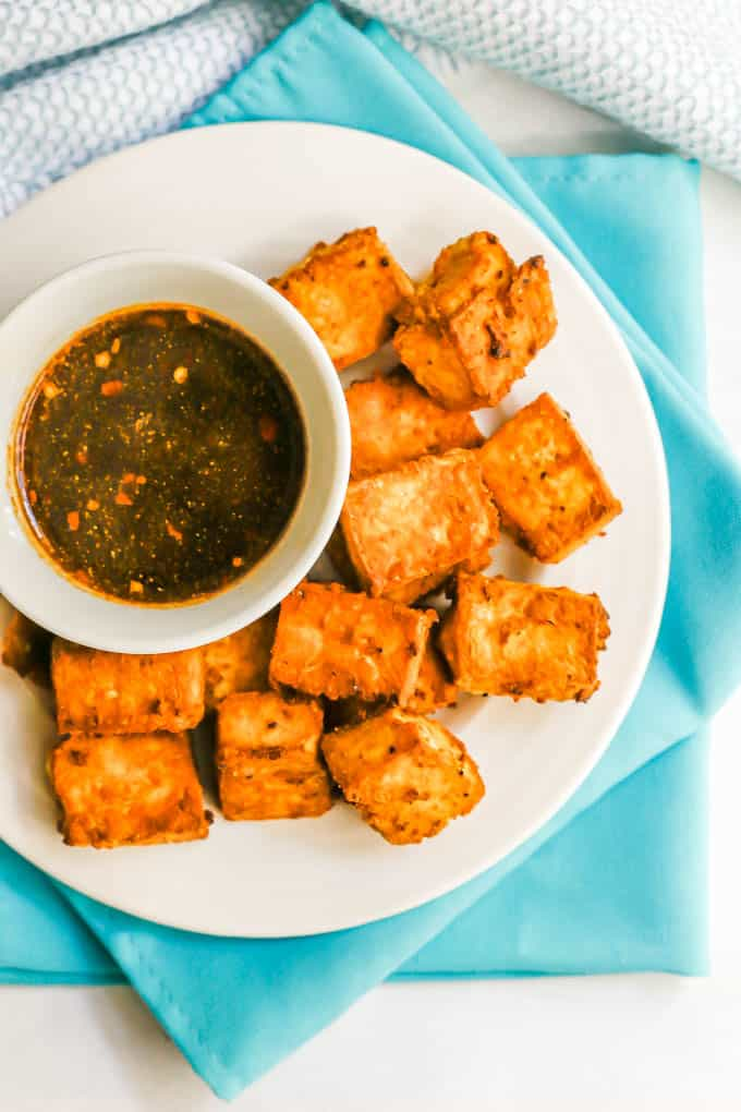 Close up of crispy tofu on a white plate with a small bowl of a brown soy sauce dipping sauce