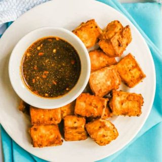 Overhead shot of a white plate with browned crispy tofu pieces and a small bowl with a soy sauce dipping sauce