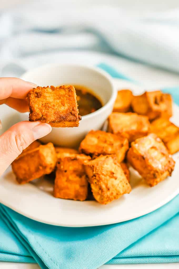 A hand holding up a golden browned and crispy tofu nugget from a plate of tofu pieces