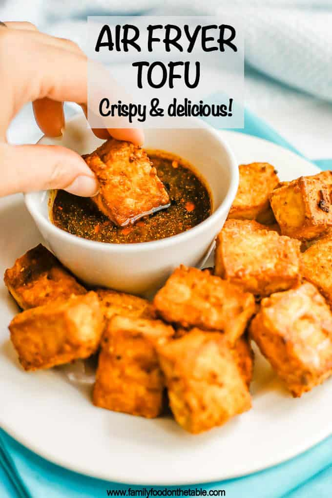 A hand dipping a crispy tofu piece into a soy sauce dipping sauce with a text overlay on the photo