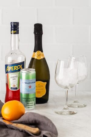Ingredients for making Aperol Spritz cocktails laid out on a counter