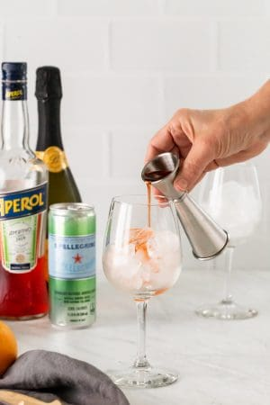A shot glass pouring out Aperol into a wine glass with ice