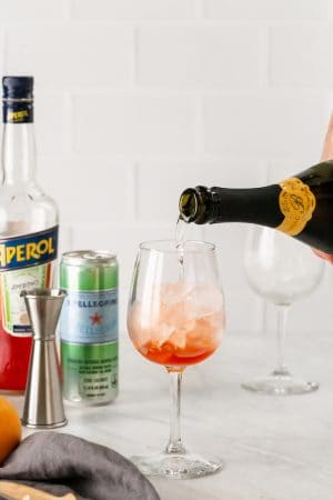 Sparkling wine being poured over ice and Aperol in a wine glass