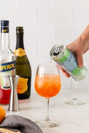 Club soda being poured in a wine glass with Aperol and sparkling wine in the background