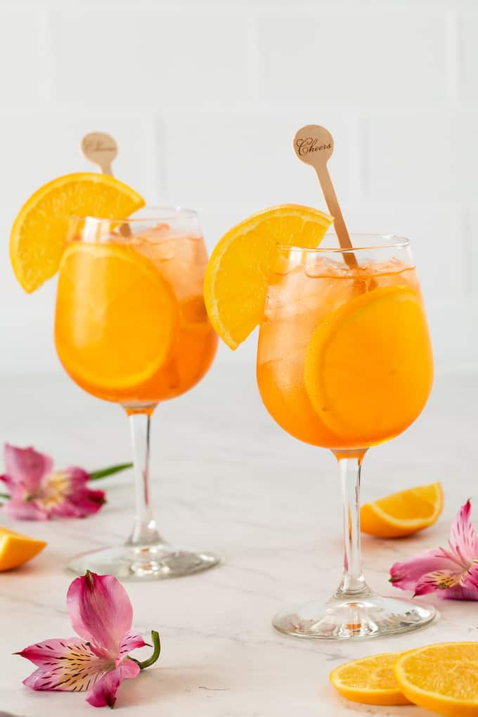 Two wine glasses with an orange cocktail and ice mixture and orange slices for garnish