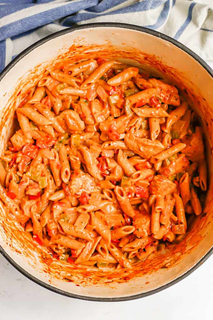 A creamy but healthy cajun chicken pasta in a large purple pot after cooking