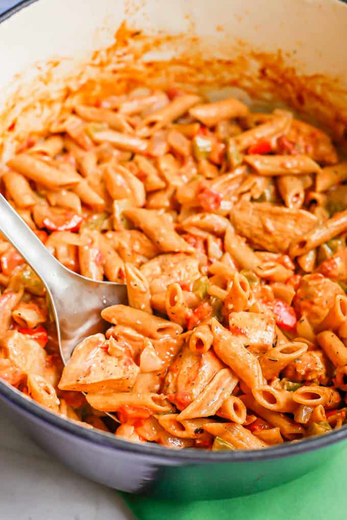 Close up of a silver serving spoon scooping up a creamy chicken pasta mixture from a large purple pot