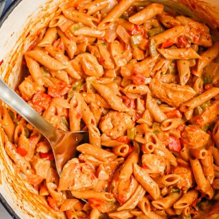 A large pot full of a creamy cajun chicken pasta with tomatoes and veggies, with a silver spoon dipped in
