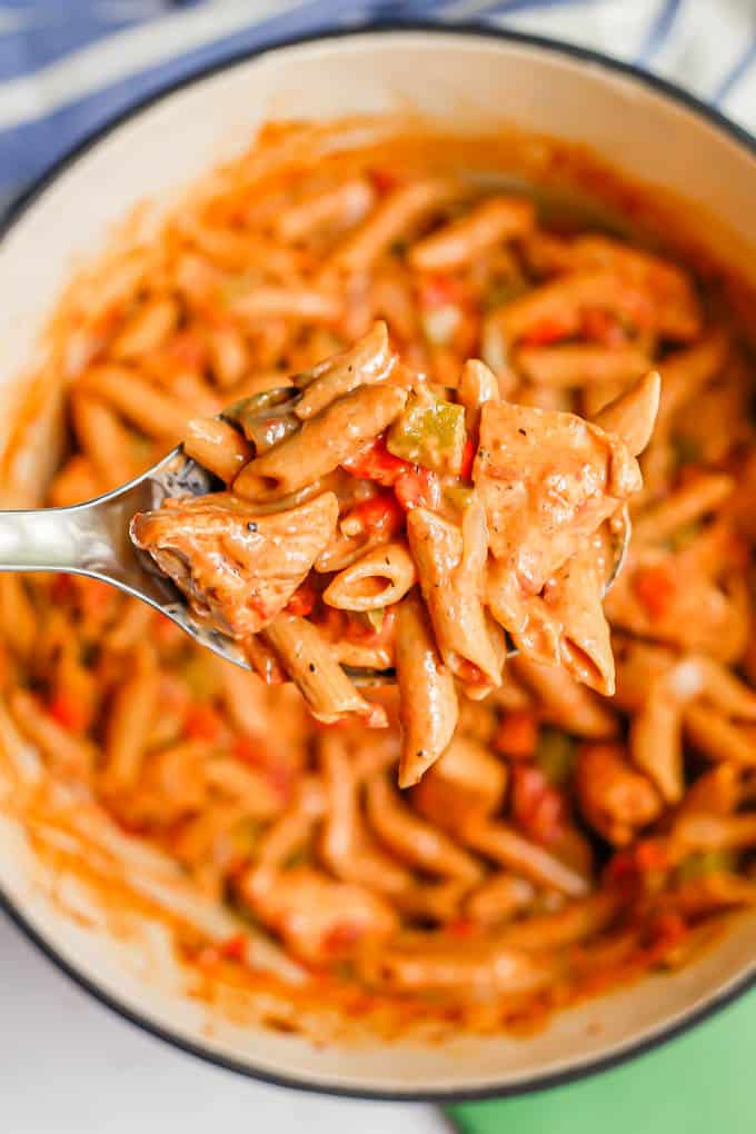 Overhead shot of a silver serving spoon lifting up a scoop of Cajun chicken pasta from a large pot