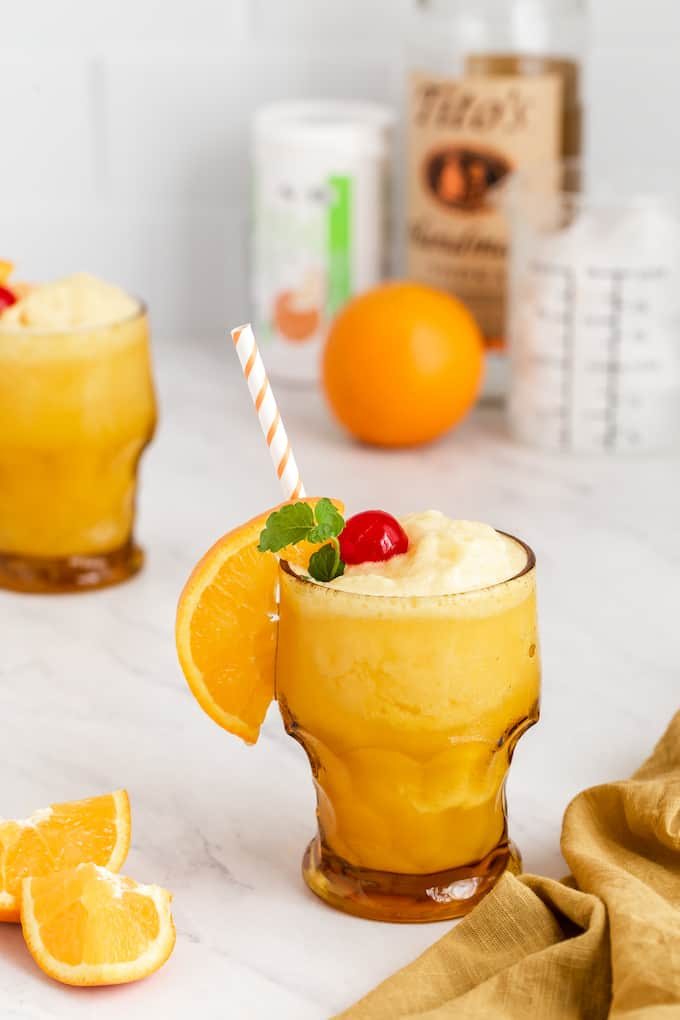 An alcoholic orange slushy in a glass with orange, cherry and mint garnishes and an orange striped straw, plus the drink ingredients in the background