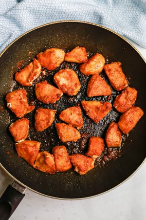 Crispy browned chicken pieces after being cooked and seared in a large skillet