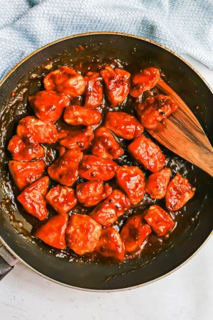 Crispy orange chicken pieces in a large dark skillet after being cooked and tossed in a sauce