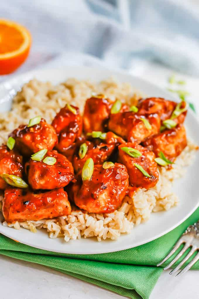 Close up of cubed orange chicken pieces served over steamed brown rice on a white plate with green onions sprinkled on top