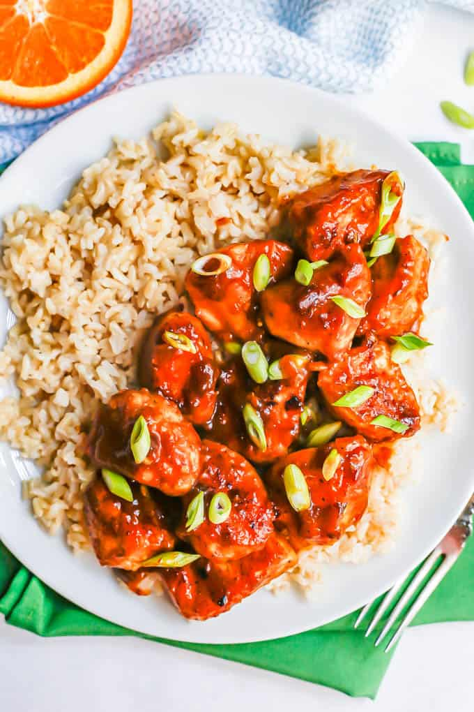 Cubed orange chicken served over steamed brown rice on a white plate with green onions sprinkled on top