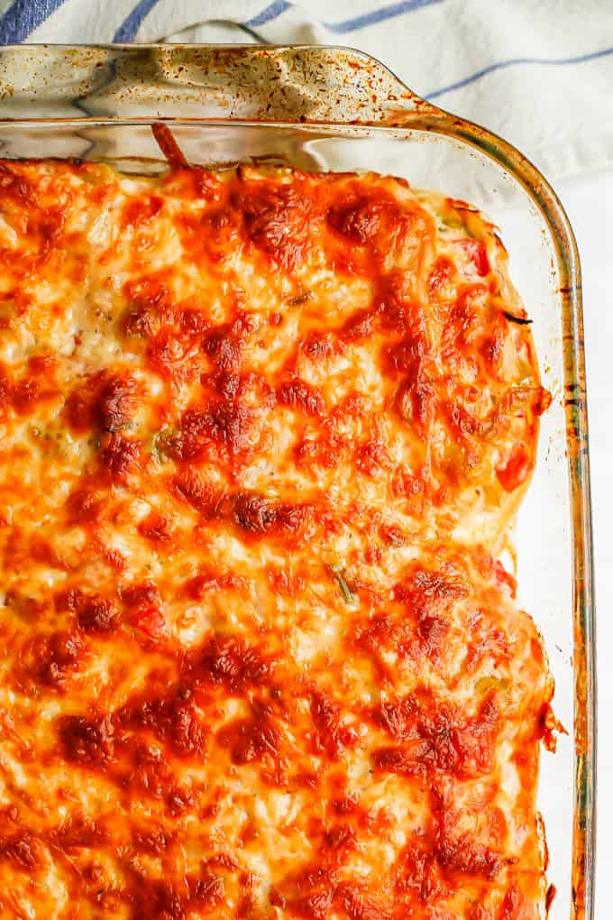 Close up of a browned baked cheesy chicken casserole in a glass casserole dish