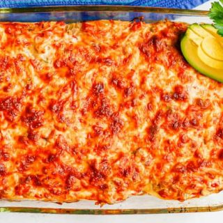 A cheesy casserole with chicken and tortillas after being baked with cilantro and avocado slices on top