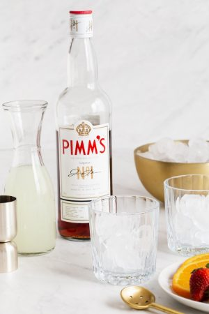 Pimm's No. 1, lemonade and glasses with ice set out to make a cocktail