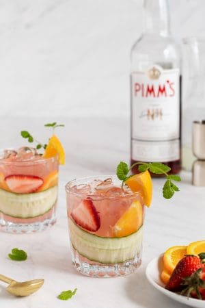 Two cocktail glasses with a fruity mixture and a Pimm's No. 1 bottle in the background