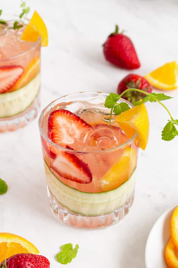 Two glasses of Pimm's Cup with fresh fruit, cucumber and extra fruit on the counter
