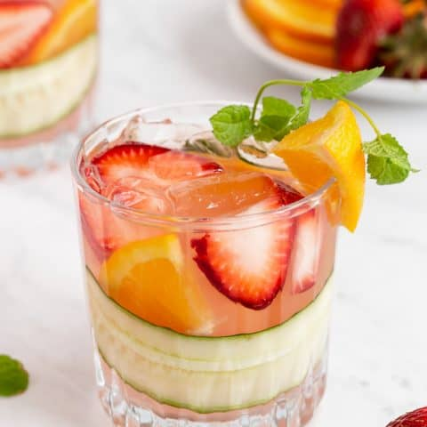 A short, clear drink glass with fruit, cucumber and Pimm's Cup cocktail with extra fruit laying around