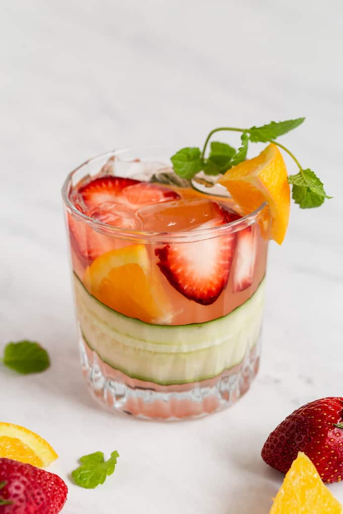 A single short, clear drink glass of Pimm's Cup with fruit and cucumber and extra fruit laying around