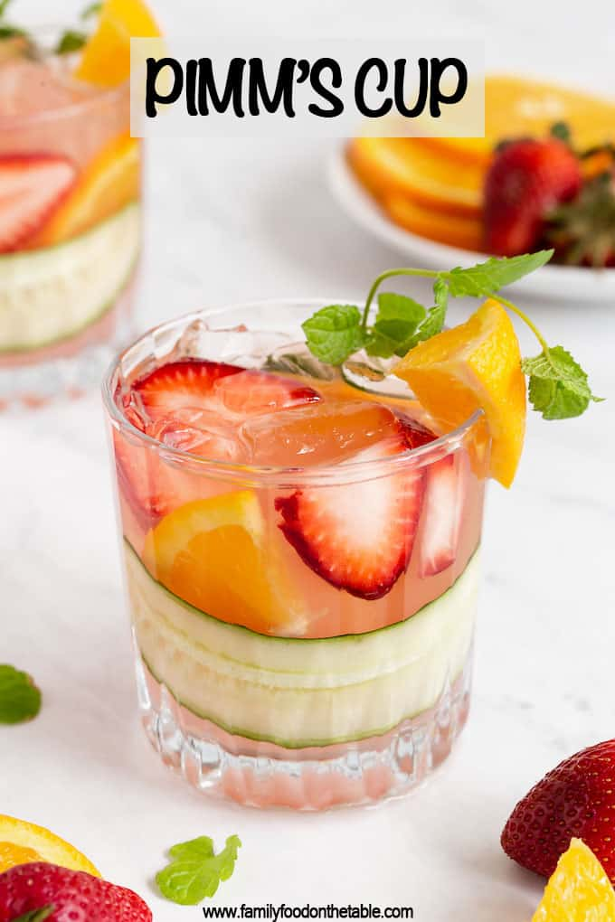 A short, clear drink glass with fruit, cucumber and Pimm's Cup cocktail with extra fruit laying around and a text overlay on the photo and another drink in the background