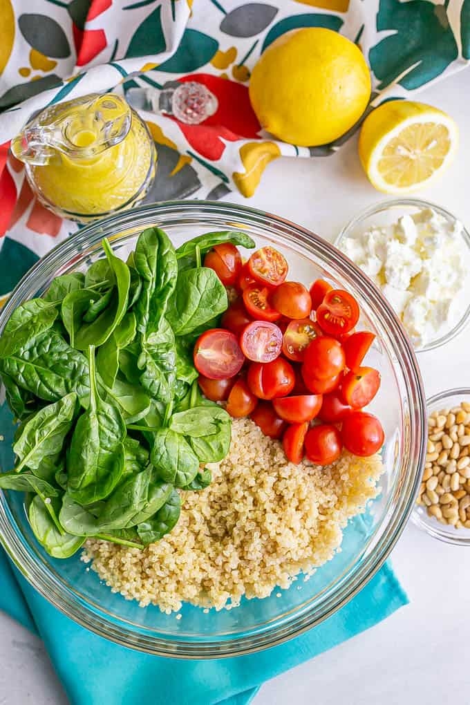 A bowl with quinoa, tomatoes and spinach and extra toppings and dressing in bowls to the side