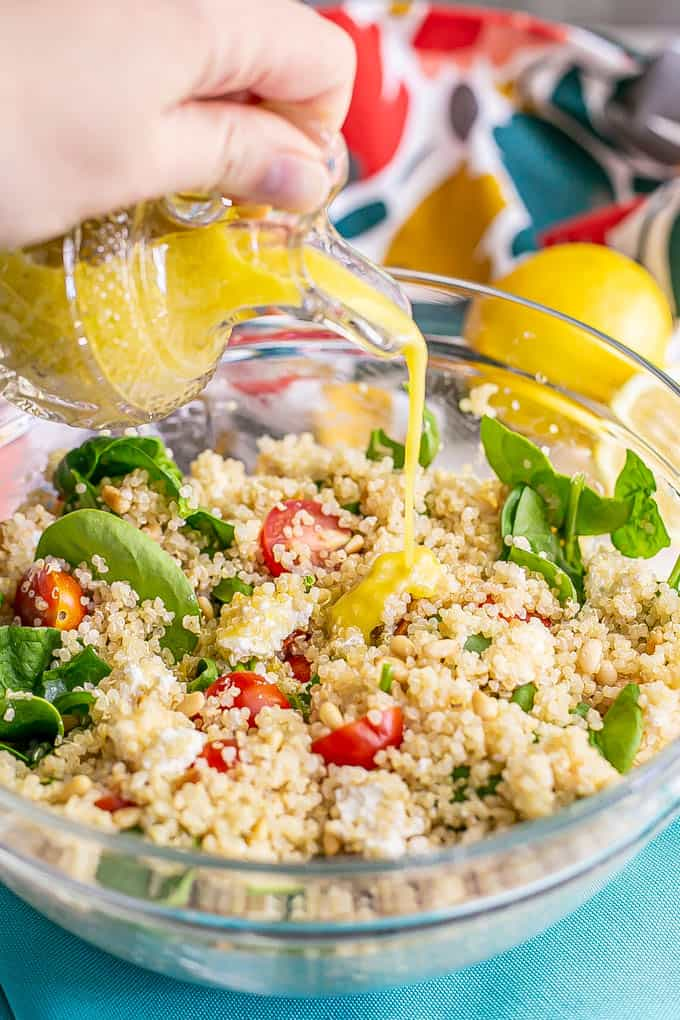 A hand pouring a lemony vinaigrette from a crystal jar over a quinoa salad with spinach and tomatoes