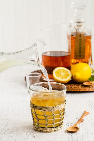 Lemonade being added to an alcoholic Arnold Palmer drink glass