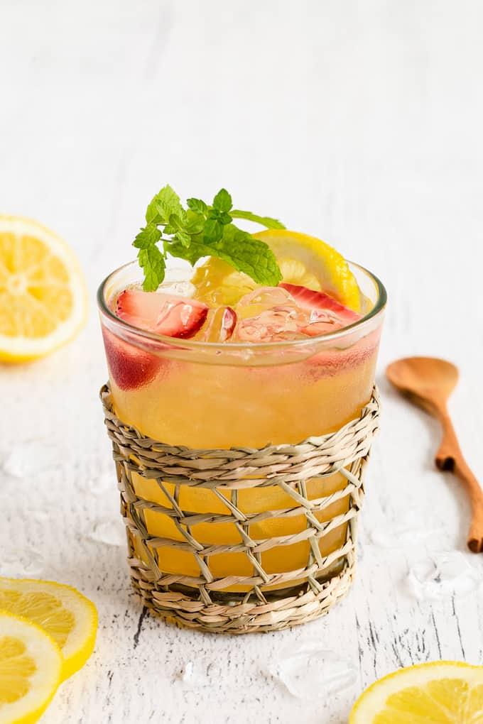 Close up of a spiked Arnold Palmer drink in a short clear glass with a woven glass holder around it and lemon slices and a small wooden spoon nearby