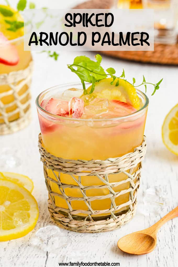 A short clear glass with a lemonade tea and bourbon drink plus lemon and strawberry garnishes and a text overlay on the photo