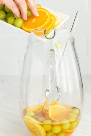 Fresh fruit being added to a large glass drink pitcher