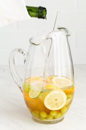 A bottle of sparkling wine being poured into a large glass pitcher that has a fruity white sangria mix in it